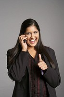 Businesswoman phoning with a mobile phone showing thumb up