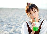 A woman drinking a cup of juice