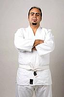 Latin man on karate outfit looking at the camera in a studio setting