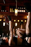 Young sexy woman doing striptease with camera in burlesque bar.
