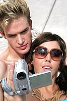 Young couple holding video camera.