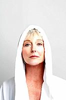 Mature woman wearing hooded bathrobe.
