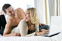 Young couple using laptop in bed.
