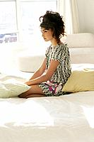 Young stylish woman sitting in bed.