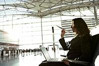 Young businesswoman throwing paper airplane in airport.
