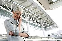 Happy mature woman on the phone in front of airport.