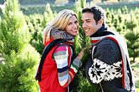 Happy young couple at Christmas tree farm.