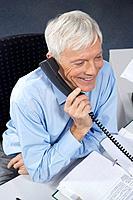Mature businessman at desk, on phone