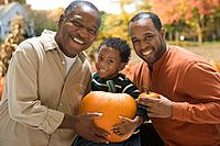 African multi_generational family holding pumpkins