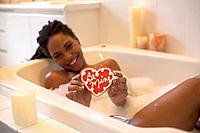 African woman in bathtub holding valentine cookie