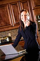 Businesswoman using a cell phone and laptop