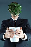 Businessman carrying potted plant