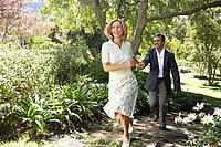 Woman and man running through garden