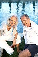 Man and woman sitting near swimming pool