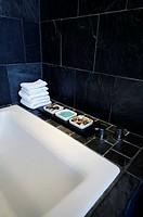 Trays of stones and bath salts on edge of bathtub