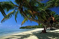 Couple sitting on the beach in the shade, Ile aux Nattes, Ste Marie, Madagascar, Indian Ocean