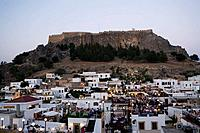 View over illuminated town in the evening to Acropolis, people sitting on terraces of restaurants, Lindos, Rhodes, Greece