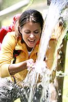 Woman drinking water from fountain in the mountains, National Park Hohe Tauern, Carinthia, Austria