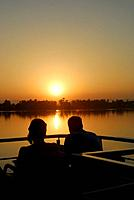 cruise on the Nile, couple on upper deck, sunset above palm trees at western bank, Nile between Luxor and Dendera, Egypt, Africa