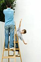 Father and son standing on ladder, boy pretending to be a plane