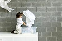 Little boy playing with laundry, smiling, side view