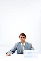 Businessman sitting at table with two different sized stacks of paper