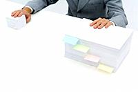 Stacks of paper with adhesive notes dividing them, man putting one hand on each stack