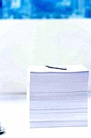Stack of paper with pen on top of it