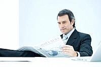 Businessman sitting at desk, reading newspaper, looking down with concerned expression
