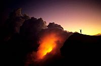 Hawaii, Big Island, Hawaii Volcanoes National Park, Lava flowing into ocean, Person standing nearby on cliff.