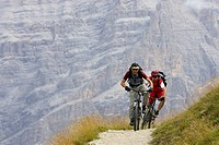 Two mountianbike riders in front of a rock face