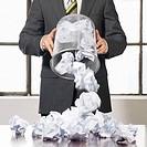 Businessman pouring trash over desk