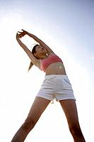 A woman stretching herself during bright sunlight
