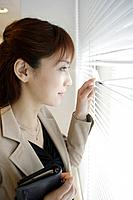 A woman looking outside through the blinds