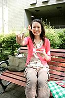 A young woman holds her food in the fork while sitting on the bench as she smiles at the camera