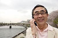 Portrait of a smiling senior man using mobile phone