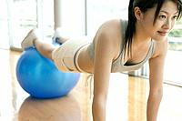 A woman works out in the gym as she performs the exercise for abs