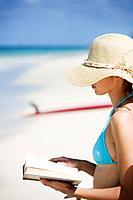 A woman reading book on beach