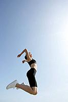 A low angle view of woman jumping in air