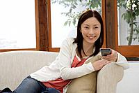 View of a young woman holding a remote control