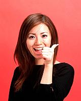Young Woman with thumb Up, Front View, Looking at Camera