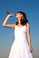 Germany, Bavaria, Young woman drinking water from bottle, portrait