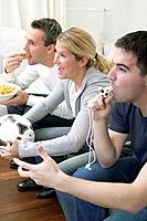 Friends watching TV with referee´s whistle, football & crisps