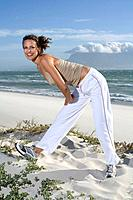 South Africa, Cape Town, Young woman exercising on beach