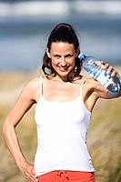 Young woman holding water bottle, portrait