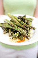 Woman holding a plate of grilled green asparagus