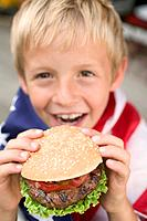 Small boy holding hamburger 4th of July, USA