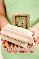 Woman holding olive soap, soap dish and brush