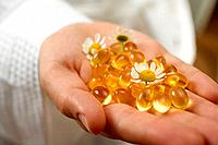 Hand holding vitamin capsules and chamomile flowers
