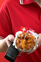 Footballer holding currywurst sausage with curry sauce & remote